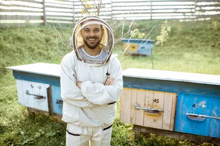 Portrait of a man as apiarists in protective uniform standing on a small traditional apiary with wooden beehives on the background Banque d'images - 132046461