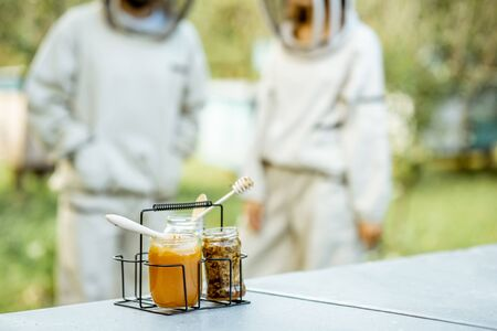 Jars with fresh honey and beeswax standing on the beehive with apiarists on the background Banque d'images - 132233176