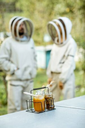 Jars with fresh honey and beeswax standing on the beehive with apiarists on the background