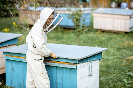 Young beekeeper in protective uniform opening beehive while working on the apiary Banque d'images - 132735710