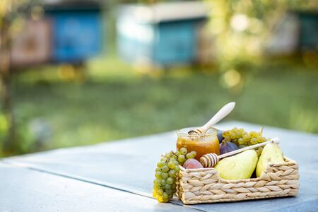 Composition of sweet fruits and jar with honey on the beehive at the apiary, image with copy space