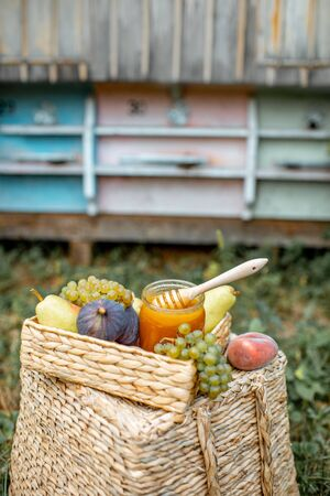 Composition of sweet fruits and jar full of honey with woooden beehives on the background at the apiary