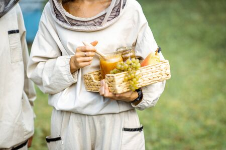 Beekeeper holding fresh honey and sweet fruits on the apiary, close-up view Banque d'images - 129801987