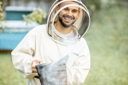 Portrait of a cheerful beekeeper in protective uniform with bee smoker on the apiary Reklamní fotografie