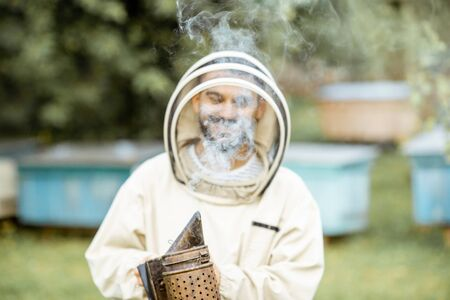 Portrait of a cheerful beekeeper in protective uniform with bee smoker on the apiary Banque d'images - 130612953