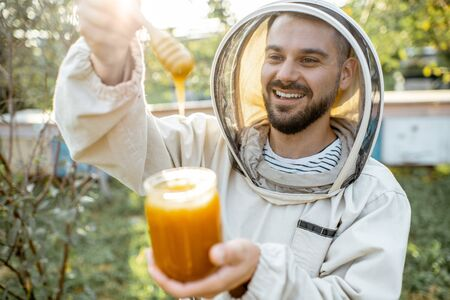 Portrait of a handsome beekeper in protective uniform standing with honey in the jar, tasting fresh product on the apiary outdoors Banque d'images - 130612974