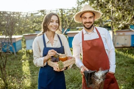 Potrait of a man and woman farmers in aprons standing with beesmoker, fruits and honey on the apiary with beehives on the background on a sunny evening