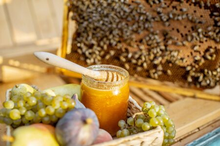 Composition of sweet fruits and jar with honey on the beehive with honeycomb on the background