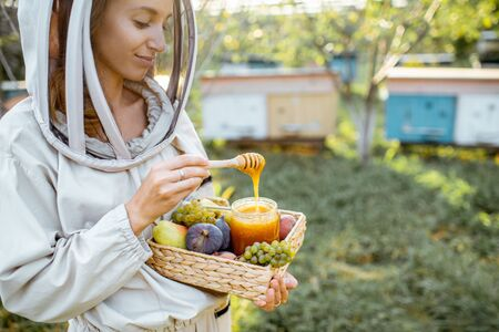 Female beekeper in protective uniform standing with fruits and honey in the jar, tasting fresh product on the apiary outdoors