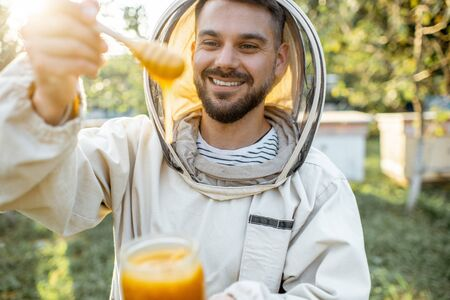 Portrait of a handsome beekeper in protective uniform standing with honey in the jar, tasting fresh product on the apiary outdoors Banque d'images - 130612981