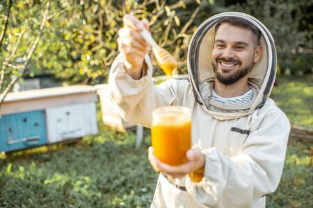 Portrait of a handsome beekeper in protective uniform standing with honey in the jar, tasting fresh product on the apiary outdoors Banque d'images - 130612983