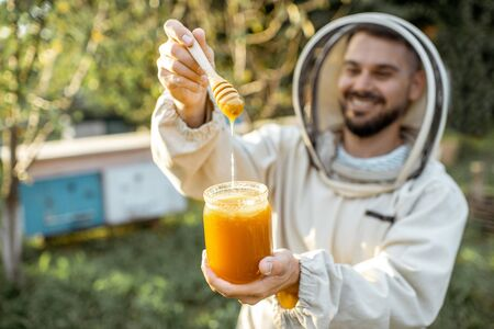 Portrait of a handsome beekeper in protective uniform standing with honey in the jar, tasting fresh product on the apiary outdoors
