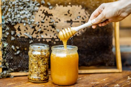 Jar with fresh honey on the beehive with honeycomb on the background Banque d'images - 129801989
