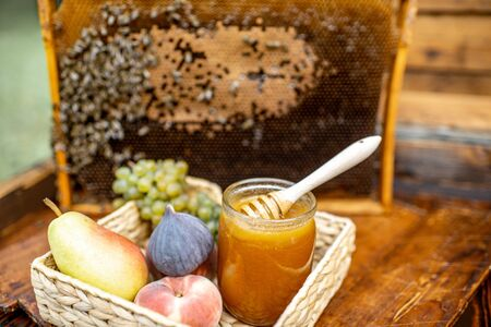 Composition of sweet fruits and jar with honey on the beehive with honeycomb on the background Banque d'images - 129801991