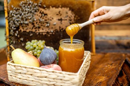 Composition of sweet fruits and jar with honey on the beehive with honeycomb on the background Banque d'images - 132232557