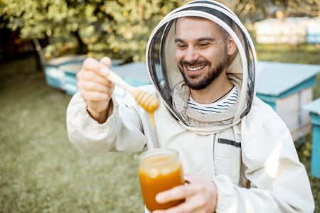 Portrait of a handsome beekeper in protective uniform standing with honey, tasting fresh product on the apiary outdoors Banque d'images - 132735719