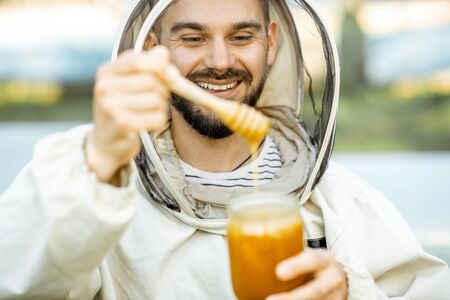 Portrait of a handsome beekeper in protective uniform standing with honey, tasting fresh product on the apiary outdoors Banque d'images - 132735718