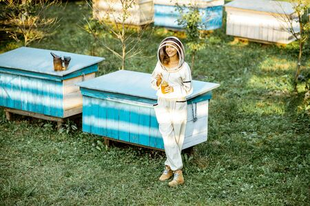 Full body portrait of a female beekeeper in protective uniform on the apiary outdoors Standard-Bild