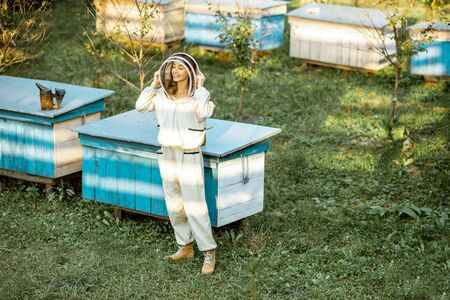 Full body portrait of a female beekeeper in protective uniform on the apiary outdoors Banque d'images - 130612991