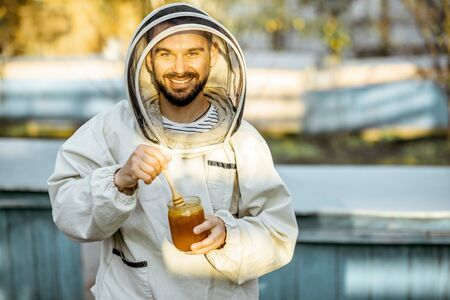 Portrait of a handsome beekeper in protective uniform standing with honey, tasting fresh product on the apiary outdoors Banque d'images - 130612993