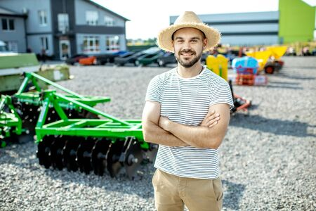 Portrait of a young agronomist standing near the plow at the outdoor ground of the shop, buying new agricultural machinery for farming