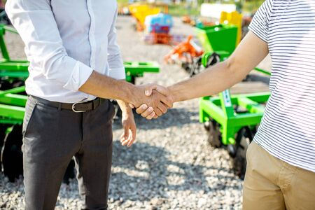 Buyer shaking hand with salesman on the open ground of the agricultural shop, having a deal, close-up view