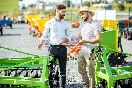Young agronomist with salesman or manager at the open ground of the shop with agricultural machinery, buying a new plow for tillage Stock fotó