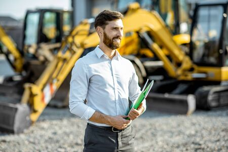 Portrait of a handsome sales consultant or manager standing on the open ground of the shop with heavy machinery for construction