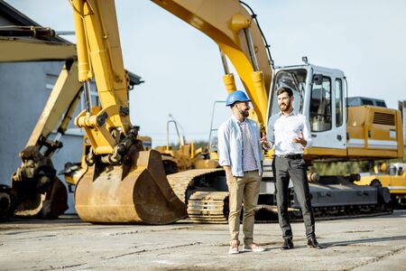 Builder choosing heavy machinery for construction, talking with a sales consultant on the open ground of a shop with special vehicles