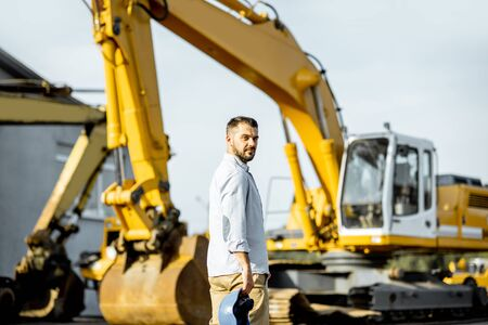 Portrait of a handsome builder standing on the open ground of the shop with heavy machinery for construction Stock fotó
