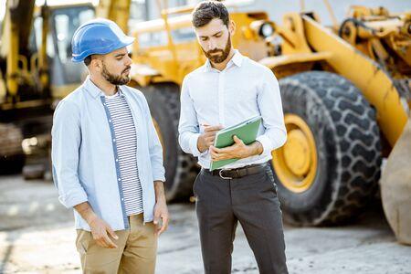 Constructor que elige maquinaria pesada para la construcción con un asesor de ventas, firmando algunos documentos en el terreno abierto de una tienda con vehículos especiales.