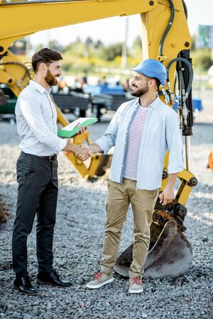 Builder choosing heavy machinery for construction shaking hands with a sales consultant on the open ground of a shop with special vehicles