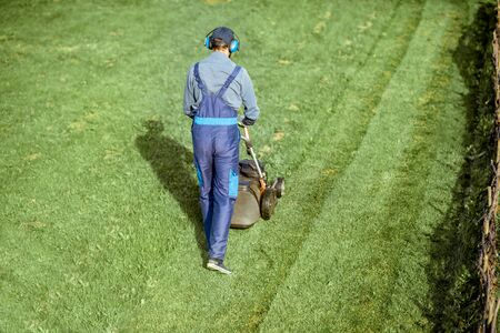 Professional gardener in protective workwear cutting grass with gasoline lawn mower on the backyard, View from above 版權商用圖片