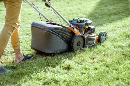 Gardener cutting grass with gasoline lawn mower on the backyard, close-up view