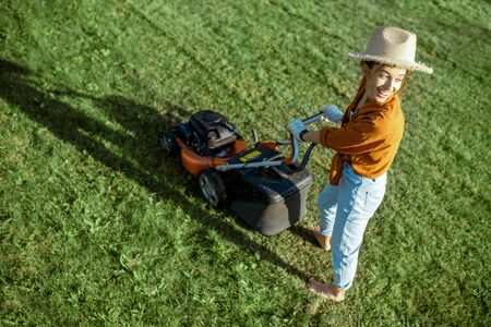 Portrait of a beautiful young woman dressed casually resting while cutting grass with lawn mower on the backyard Stock fotó - 130135549