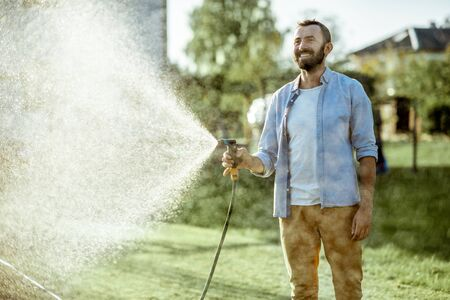 Handsome man watering green lawn, sprinkling water on the grass during a sunny morning on the backyard. Lawn care concept