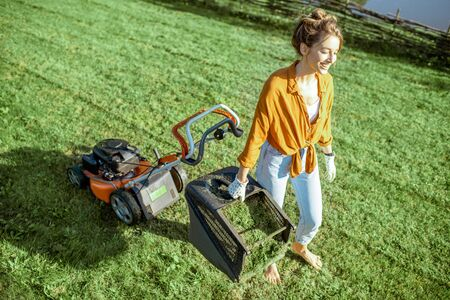 Beautiful young woman carrying basket full of cut grass while gardening with lawn mower on the backyard in the countryside