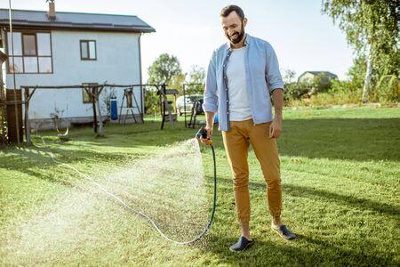Hombre guapo regando el césped verde, rociando agua sobre el césped durante una mañana soleada en el patio trasero. Concepto de cuidado del césped