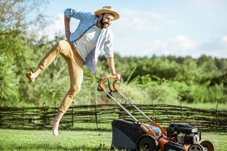 Playful man jumping while cutting grass with gasoline lawn mower, enjoying gardening process on the backyard