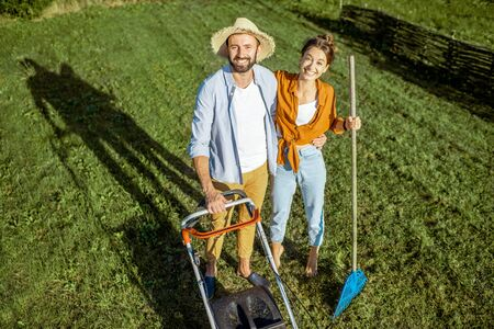Portrait of a young couple standing together on the green lawn while cleaning backyard with lawn mower and rakes 版權商用圖片