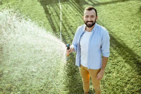 Handsome man watering green lawn, sprinkling water on the grass during a sunny morning on the backyard. Lawn care concept 版權商用圖片 - 130072724