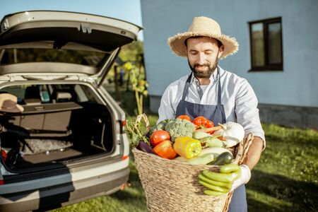 Portrait of a handsome man wearing straw hat with basket full of freshly picked up homegrown vegetables near the car at the countryside 版權商用圖片