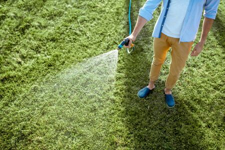 Man watering green lawn, sprinkling water on the grass with water pistol, close-up with no face