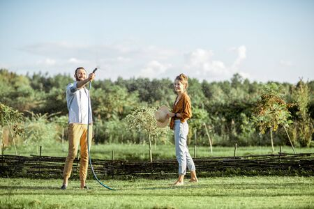 Young man and woman watering green lawn, taking care of the beautiful backyard in the countryside