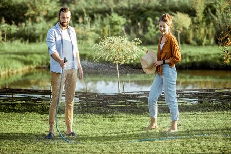 Young man and woman watering green lawn, taking care of the beautiful backyard with lake on the background