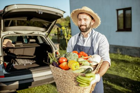 Portrait of a handsome man wearing straw hat with basket full of freshly picked up homegrown vegetables near the car at the countryside Reklamní fotografie
