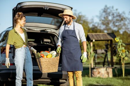 Man and woman carrying basket full of freshly picked up homegrown vegetables near the car at the countryside