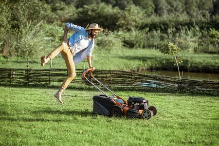 Playful man jumping while cutting grass with gasoline lawn mower, enjoying gardening process on the backyard
