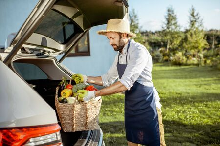 Handsome farmer in apron and straw hat putting a basket full of freshly picked vegetables into the car trunk at a country cottage Reklamní fotografie