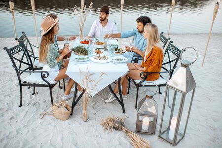 Group of young friends having a festive dinner at the beautifully decorated place with dining table, lanterns and torches on the sandy beach